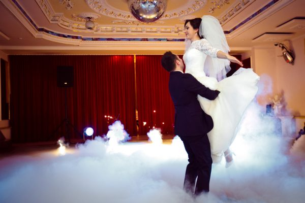happy elegant gorgeous married couple performing first dance with heavy smoke and fireworks in a stylish restaurant